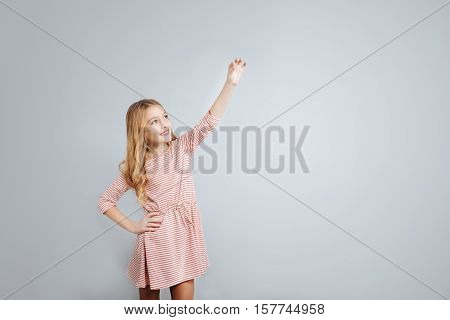 Full of gladness. Cheerful cute little girl holding hand up and smiling while standing isolated on gray background