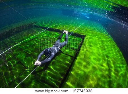 Free diver training without fins (dynamic apnea) in the swimming pool with green moss bottom