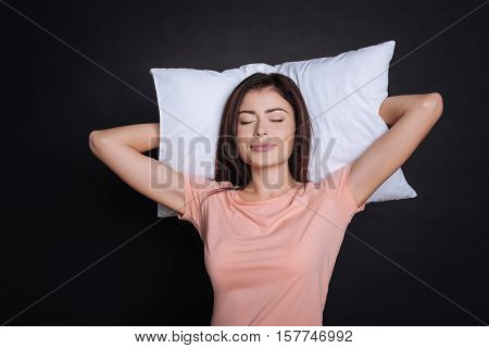 Have a substantial sleep. Content beautiful young woman holding head on the pillow and sleeping while standing on black background