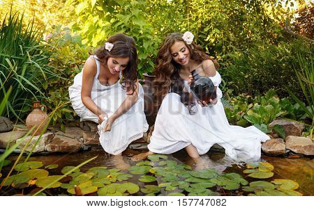 Two cute sisters in white dresses at the pond with water lilies. Women draw water in small clay pitcher. Rural population