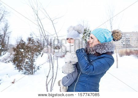 Mother and baby daughter on a walk in a winter park. Happy family. Childhood and parenthood happiness.