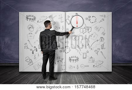 A businessman full-height standing back to us holding a magnifier looking at the giant notebook with a lot of pencil financial drawings in it. Business and finance. Infographics and analysis.