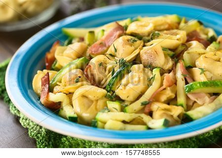 Baked cheese tortellini or belly button pasta with zucchini bacon and thyme photographed with natural light (Selective Focus Focus in the middle of the dish)