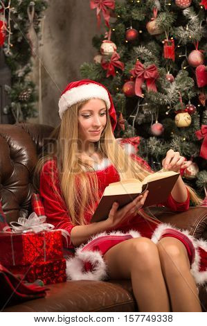 blond woman dressed as Santa at the Christmas tree sitting on the couch with a book in their hands