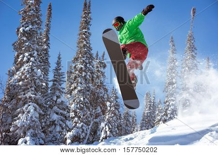 Snowboarder jumps in forest. Freeride snowboarding in Sheregesh ski resort