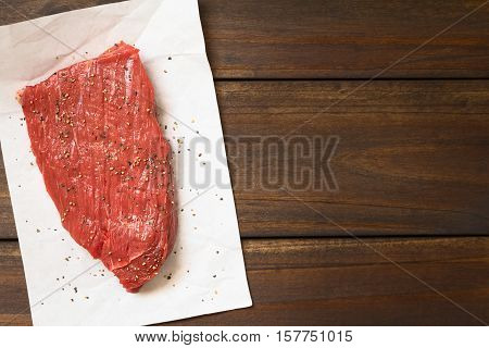 Fresh raw boneless beef meat with ground black pepper photographed overhead with natural light (Selective Focus Focus on the top of the slice)