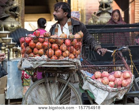 KATHMANDU NEPAL - NOV 11 2016: a nepalese man on the street sell local fruits in Kathmandu Nepal. The basic branch of economy is agriculture (76% of working population) in Nepal.