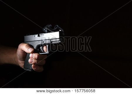 pistol in his hand in the dark closeup