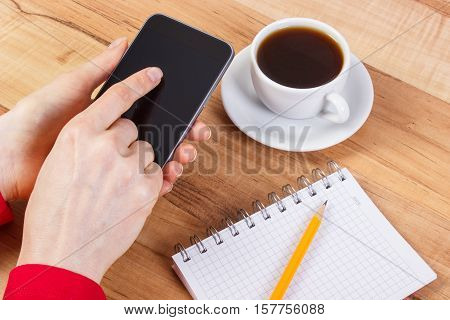 Hand Of Woman Using Mobile Phone, Notepad For Writing Notes, Cup Of Coffee