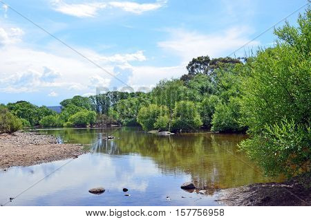 Tranquil sandy and pebbly riverbank at the head of the Shoalhaven River, Southern Tablelands, New South Wales, Australia. poster
