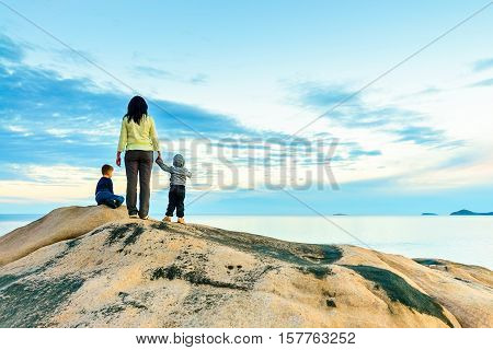 Mother with kids at the edge of the rock at Port Elliot South Australia