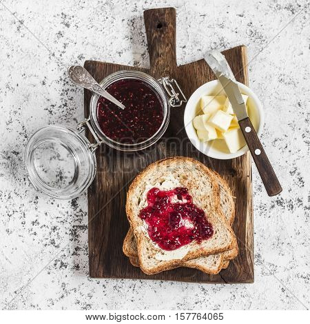 Traditional breakfast - toast with butter and jam. On a wooden board on light background top view
