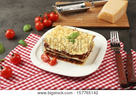 Plate with portion of tasty lasagna on napkin