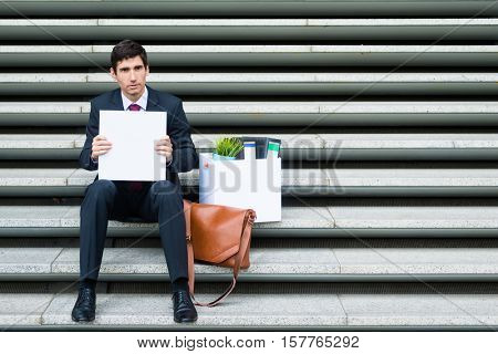 Disconsolate businessman holding a blank sign as he sits on a flight of steps in town with his briefcase and office files after being made redundant