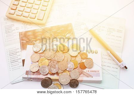 Business, finance savings or mortgage background concept ; Coins, Thai money, pen, calculator and savings account passbook on white background