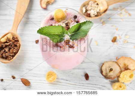 Healthy and tasty breakfast of berry milkshake with dry fruits and mint on wooden table