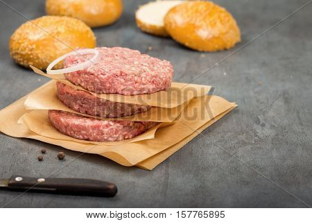 Raw ground beef meat cutlets on paper close up