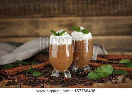 Delicious chocolate milk dessert with coffee beans and mint on wooden background