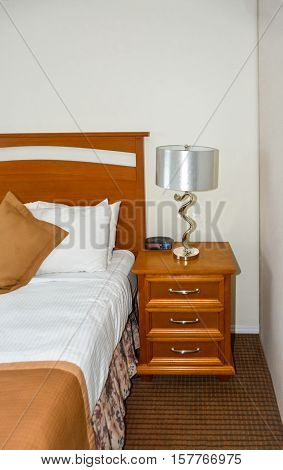 Silver lamp and radio watch on bedside table beside the bed