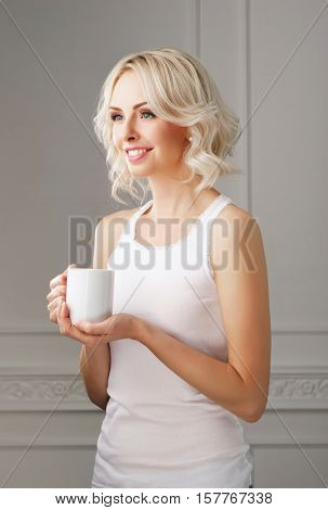 Young and beautiful woman drinking coffee and looking it to the window