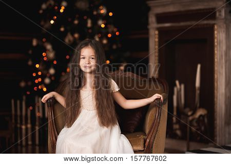 Smiling baby girl 4-5 year old wearing trendy white dress sitting in vintage chair in room over Christmas tree with lights. Looking at camera. Holiday season.