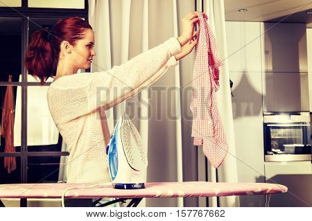 Red-haired Young Beautiful Woman Ironing Clothes