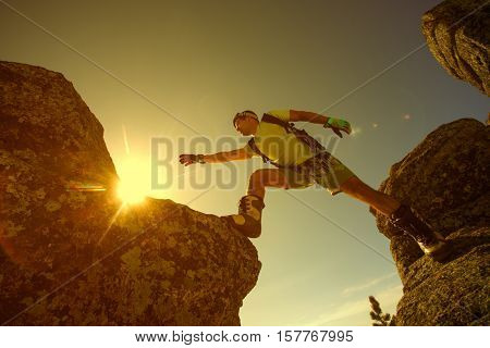 Conceptual photo climber on the summit in the rays of the setting sun