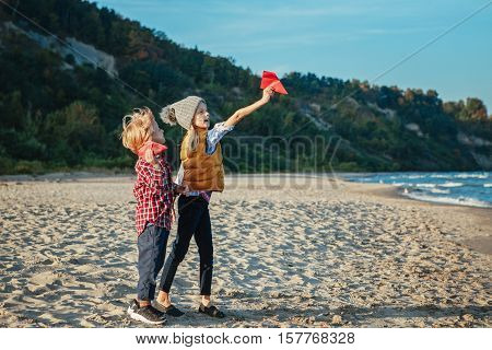 Group portrait of two white Caucasian children kids older sister and younger brother playing paper planes on ocean sea beach on sunset outdoors happy lifestyle childhood concept