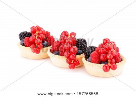 Fresh ripe berries in tartlets isolated on white background.