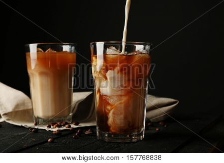 Pouring cream into a glass with iced coffee on wooden table and black background
