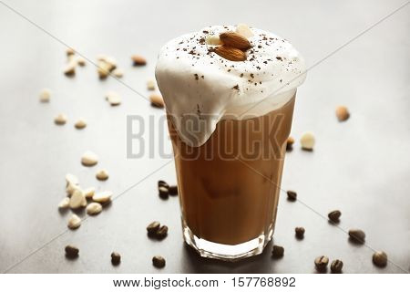 Glass of iced coffee and nuts on grey background