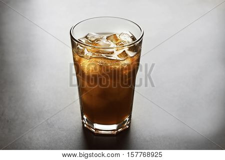Glass of iced coffee on grey background