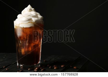 Iced coffee with cream on table and black background