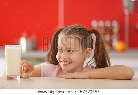 Cute little girl with glass of fresh milk at kitchen