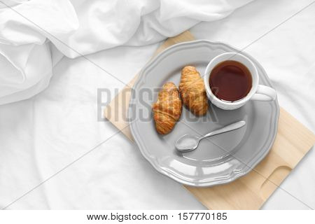 Cup of tea and croissants wooden tray. Breakfast in bed