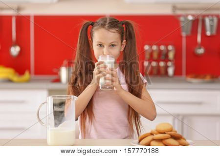 Cute little girl drinking fresh milk at kitchen
