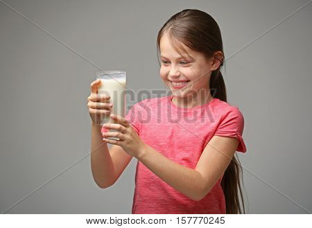 Cute little girl with glass of fresh milk on gray background