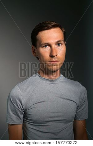 Young man in t-shirt on gray background.