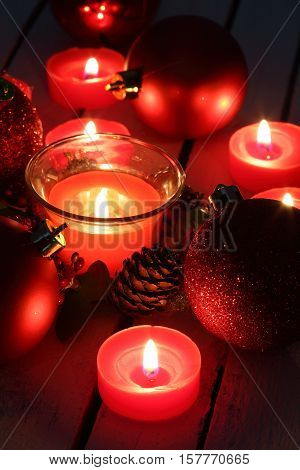 Red Christmas balls and candles close up