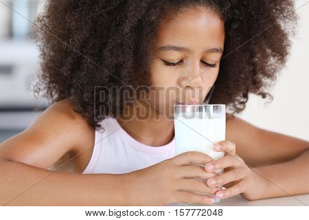 Curly African-American girl drinking milk for a breakfast in the kitchen