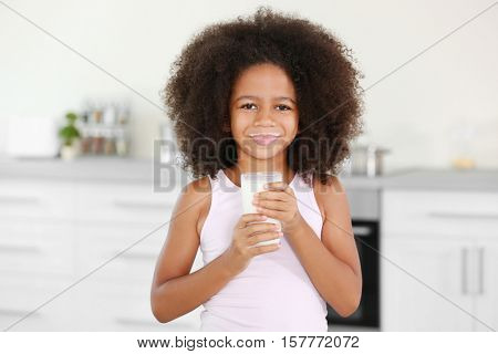 Curly African-American girl with glass of milk in the kitchen
