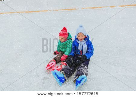 happy little boy and girl skating together, winter kids sport