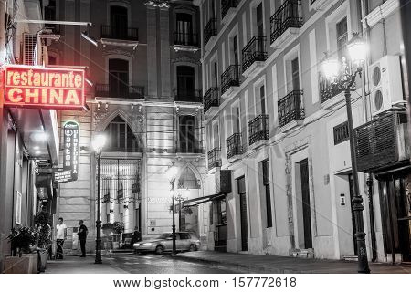 Alicante, Spain- September 9, 2016; Back street at night desaturated effect long exposure red Chinese Restaurant sign against monochrome in Alicante Spain street and building scene