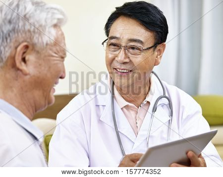 asian doctor using tablet computer to explain health condition to a senior patient happy and smiling