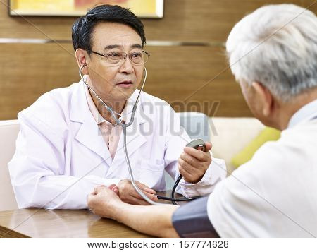 asian doctor measuring blood pressure of a senior patient using sphygmomanometer