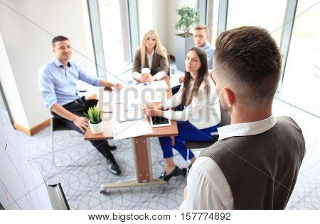 Businessman giving a presentation on flipchart. Teamwork concept