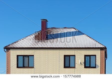 roof cottage with snow against the blue sky