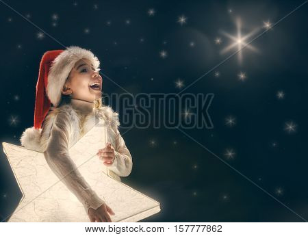 Merry Christmas and happy holidays! Cute little child girl with xmas star. Kid enjoy the holiday. Portrait kid on dark sky background. Christmas legend concept.