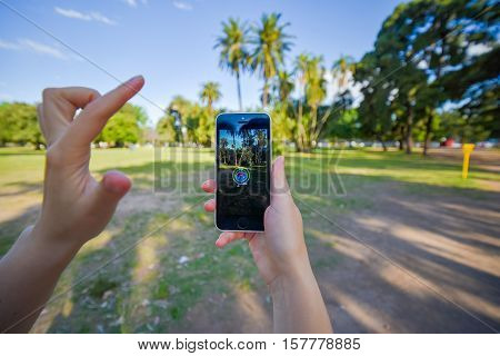 Buenos Aires, Argentina - Nov 11, 2016: Apple iPhone 5c held in one hand showing its screen with Pokemon Go application. Palms on the background.
