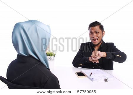Young Businessmen Pointing To His Watch With A Serious Unimpressed Expression As He Shows A Colleagu